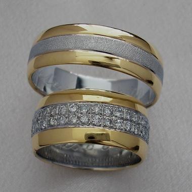 Snubní prsteny z bílého a žlutého zlata. Plocha je rozdělena podélnými drážkami na tři nestejné části. Prostřední širší část z bílého zlata je zdobena třpytivou texturou, která je v dámské variantě osázena dvěmi řadami diamantů po celém obvodu prstenu. Krajní části prstenu jsou z lesklého žlutého zlata.