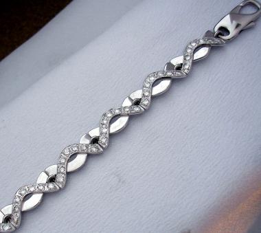 Náramek vyrobený z bílého zlata tvořený dvěmi vzájemně se prolínajícími liniemi, z nichž jedna je po celé délce zdobená diamanty.