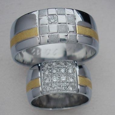 Snubní prsteny z bílého a žlutého zlata. Plocha je rozdělena podélnými drážkami na tři nestejně velké části. Střed prstenu zdobí šachovnice z matných a lesklých čtverců. Pánský prsten je zdoben jedním diamantem, v dámském provedení je diamanty osázena celá plocha šachovnice.