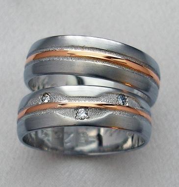 Snubní prsteny z bílého a červeného zlata vyrobené na přání zákazníka. Prsteny jsou rozdělené podélnými drážkami na tři části. Prostřední drážka z červeného zlata je lemována třpytivou texturou po obou stranách. Dámský prsten je navíc doplněn o tři vsazené diamanty.