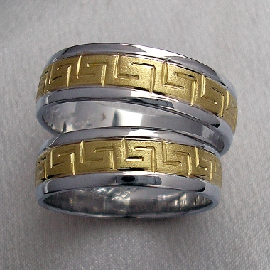 Snubní prsteny z bílého a žlutého zlata. Prsteny jsou rozdělené drážkami na tři části. Prostřední nejširší část ze žlutého zlata je zdobena řeckým vzorem.
