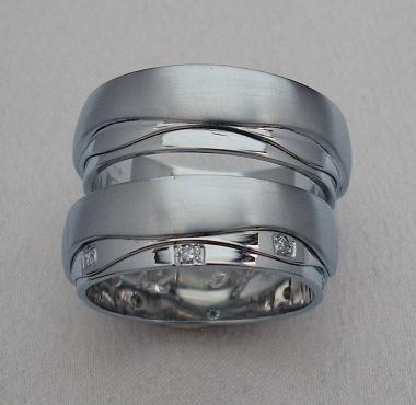 Velmi netradiční snubní prsteny z bílého zlata jsou rozděleny nepravidelnými drážkami na tři nestejně velké části. Největší část je matovaná, zbylé dvě mají lesklý povrch zdobený, v dámské variantě, vsazenými drobnými diamanty.