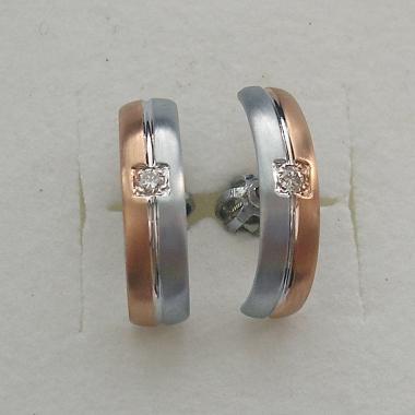 Náušnice z bílého a červeného zlata do sady k snubním prstenům. Náušnice jsou rozděleny drážkou na dvě půlky podle barvy zlata, uprostřed je zasazený drobný diamant.